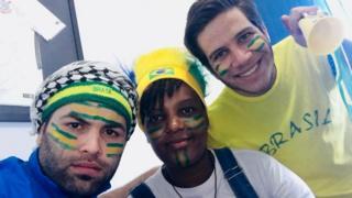 A moçambicana Lara Lopes vendo o jogo Brasil x México com dois amigos sírios