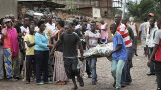Men carry away a dead body in the Nyakabiga neighborhood of Bujumbura