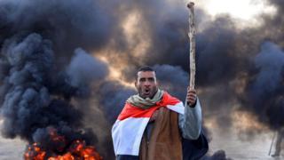 أحد المحتجين أثناء مساهمته بحرق الإطارات لإغلاق الطرق في مدينة النجف