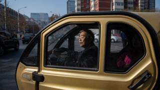 A man sits in an electric car in China