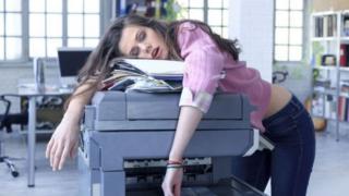 Una muchacha sobre una fotocopiadora