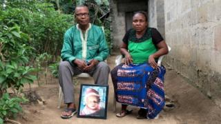 Barinaadaa Saturday e Chief Bira Saturday sentados do lado de fora da casa, com um retrato do filho falecido.