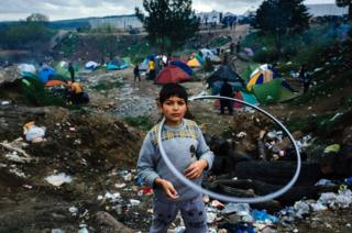 A girl plays with a hula hoop in a makeshift camp