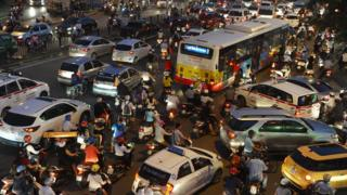 Motorcyclists among rush hour traffic at an intersection in Hanoi