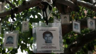 Laminated images of the 43 missing students from the Isidro Burgos rural teachers college hang from a tree in Mexico City, Friday, Aug. 26, 2016.