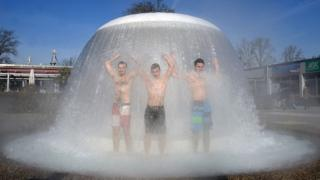Visitors of the 'Sonnenbad' open-air public swimming pool take a shower at a water mushroom during the opening of the season on February 26, 2016 in Karlsruhe, southern Germany