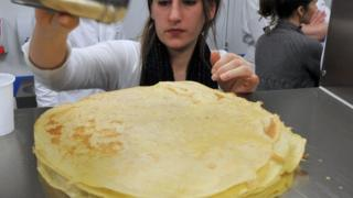 A student sprinkles sugar as she takes part in a class to learn how to make French sweet pancakes known as 'crepes'