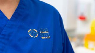 A person wearing NHS Wales uniform