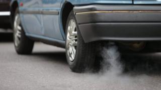 The exhaust pipe of a blue car with white smoking coming out.