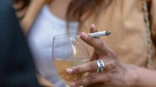Mujer bebiendo y fumando