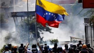 A demonstrator waves a Venezuelan flag during riots at a march to state Ombudsman's office in Caracas, Venezuela May 29, 2017.