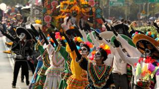 People dressed in skeleton make-up dance in colourful parade