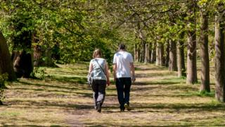 Two people walking in Greenwich Park, London
