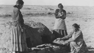 Un grupo de mujeres navajo hornean pan en un horno de barro en esta imagen de la primera mitad del siglo XX.