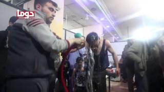 man pouring water over the head of another man (still from video)