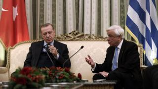 Greek President Prokopis Pavlopoulos talks with his Turkish counterpart Recep Tayyip Erdogan during a meeting at the Presidential Mansion in Athens