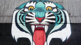 A colourful painting of a tiger with a doorway leading into its mouth