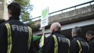 Firefighters with a United for Grenfell placard