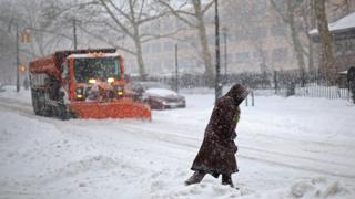 A woman crosses the street in front of a snow plow in the Brooklyn in New York City