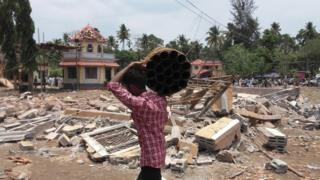 A man walks carrying empty shells of fireworks past a collapsed building after a massive fire broke out during a fireworks display at the Puttingal temple complex in Paravoor village, north of Thiruvananthapuram, southern Kerala state, India,