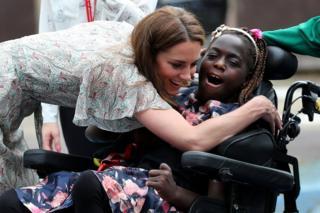 The Duchess of Cambridge hugs a girl