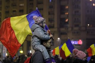 A child carries a Romanian national flag during a demonstration in Bucharest, Romania, 5 February