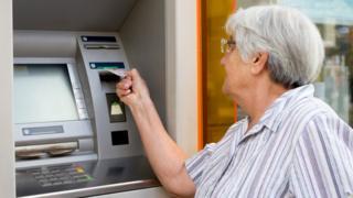 Older woman using cash machine