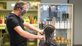 Conrad Blandford, owner of Conrad Blandford Hairdressing salon, Sheffield wears PPE (Personal Protective Equipment) and a protective face mask works with a client's hair in Sheffield, UK, as lockdown ease allows hair salons to reopen across the UK.