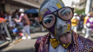 A disguised and painted man does a tongue trick during a street parade in Cape Town on 2 January