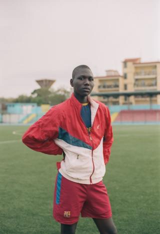 A boy wearing a tracksuit in a stadium