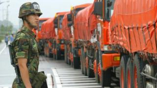 South Korea solider stands near trucks