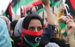 online dating یک زن لیبی با پرچم لیبی کنار او روبرو می شود تا خواستار خاتمه خلیفه افشار شود