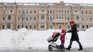 A woman pushes a pram past piles of snow in Moscow