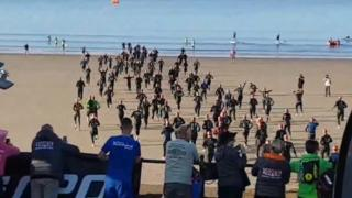 Athletes run into the sea at Barry