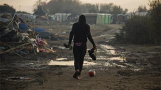 A man walks across Calais migrant camp