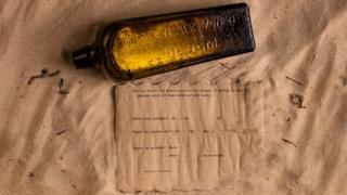 La botella y la nota sobre la arena. (Foto: kymillman.com)