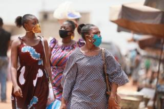 in_pictures Women wear face masks with kente and wax print designs as they walk through a market.