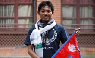 Japanese climber Nobukazu Kuriki poses with a Nepalese flag during a press conference in Kathmandu, Nepal, on 23 August