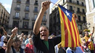 A man waves a stelada (pro-independence Catalan flag) during a protest against the arrest of two Catalan separatist leaders in Barcelona on October 17, 2017