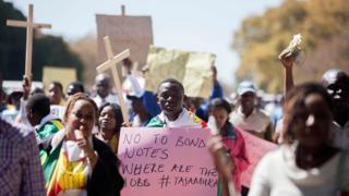 """Protesters in Harare, Zimbabwe, holding crosses and one holding a sign reading """"No to bond notes, where are the jobs"""" - Wednesday 3 August 2016"""