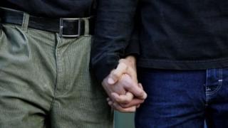 мужчины держатся за руки
