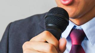 Una persona hablando por un microfono