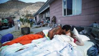 Una pareja se besa mientras está acostada sobre un colchón a las afueras de su casa.