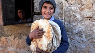 Boy holds bread in Aleppo province, Syria
