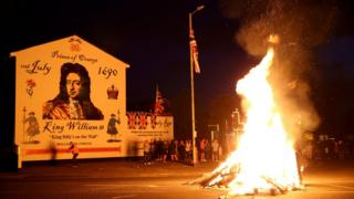 A bonfire burning in front of a William of Orange Mural