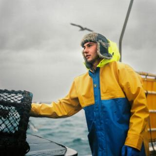 A fisherman stands with a net