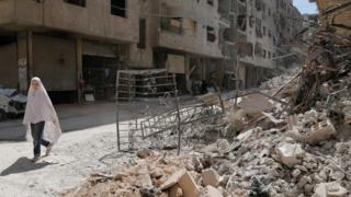 فتاة تسير أمام حطام مبنى مُهدم في عين ترما في الغوطة الشرقية قبل اتفاق وقف إطلاق النار الأخير