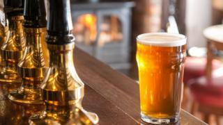 Стакан с пивом на стойке бара