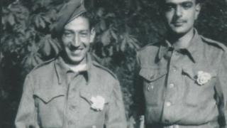 Jorge Sanjinez sosteniendo un fusil y sonriendo, junto a otro soldado.