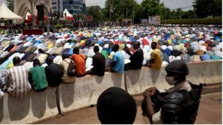 Malian riot policemen keep an eye on Muslims gathering for the Friday prayer in the Independence square in Bamako on June 5, 2020.